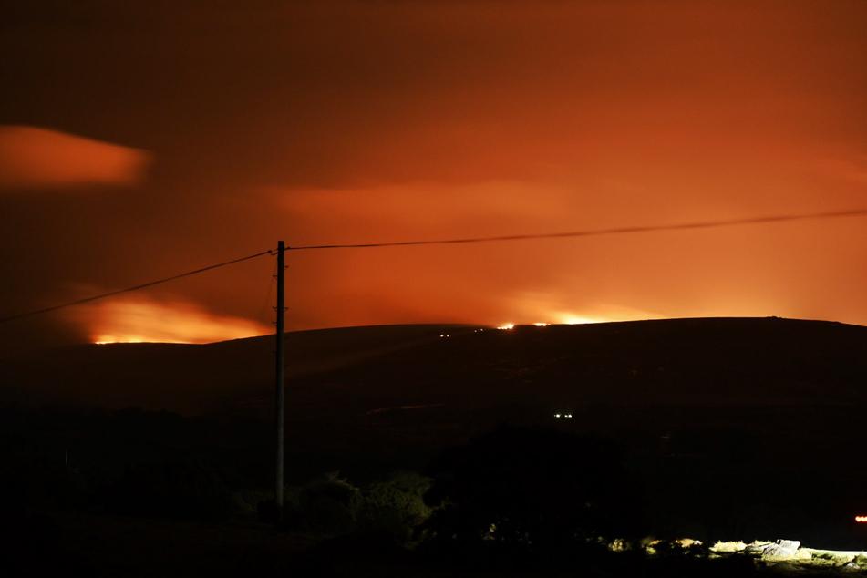 Feuer ist am Horizont zu sehen, das im Dartmoor in der englischen Grafschaft Devon ausgebrochen ist. Die Moor- und Heidelandschaft ist für ihre bronzezeitlichen Gräber und Siedlungsspuren wie beispielsweise Steinkreise bekannt.