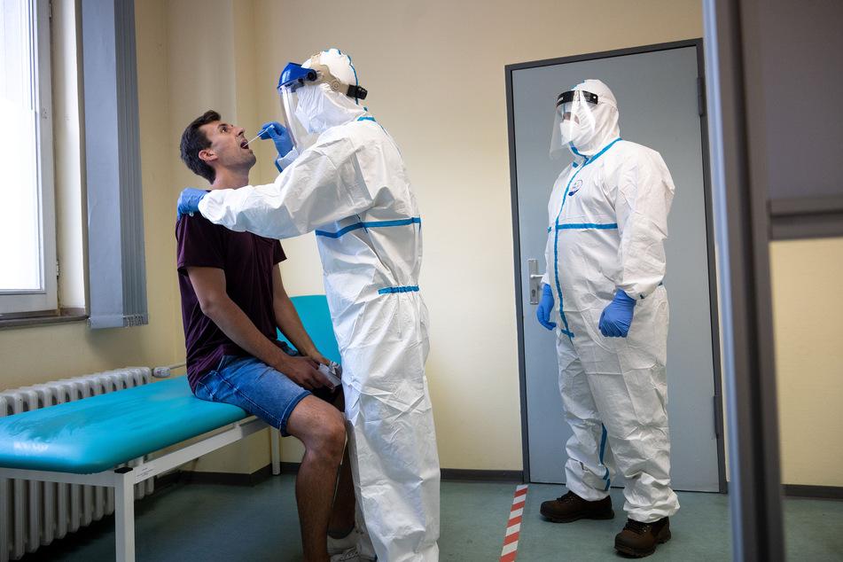 Ein Mitarbeiter des Gesundheitsamts demonstriert bei einem Mann einen Corona-Test per Rachenabstrich.
