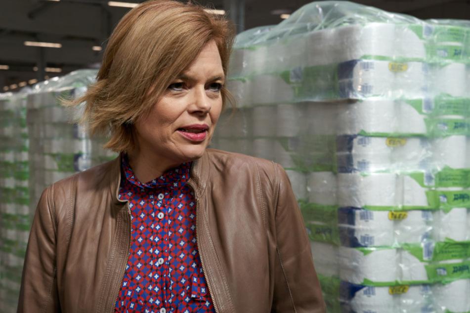 Julia Klöckner (CDU), Bundeslandwirtschaftsministerin, steht beim Besuch des Zentrallagers des Lebensmitteldiscounters ALDI vor Paletten voll Toilettenpapier.