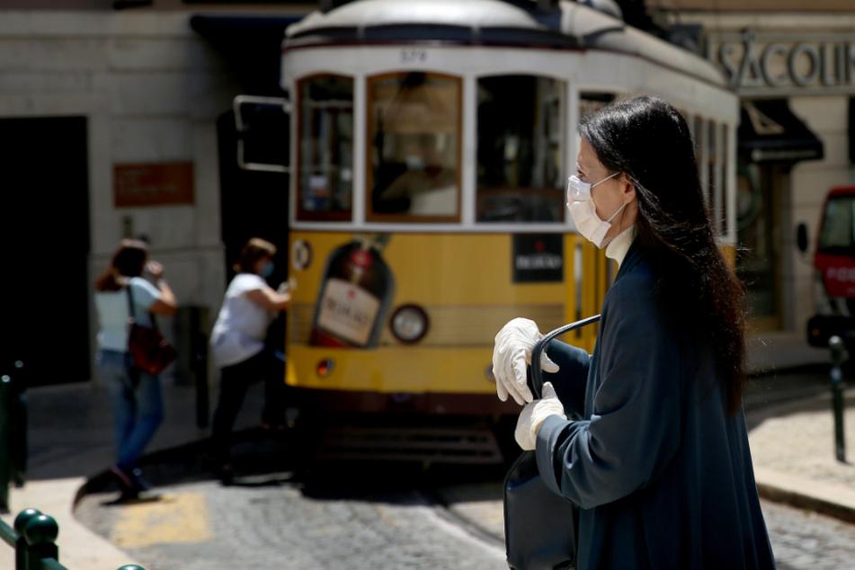 Portugal, Lissabon: Eine Passantin trägt einen Mundschutz und Schutzhandschuhe.