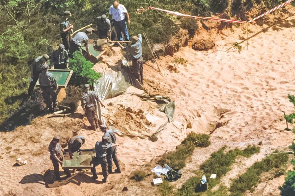1995 wurde der achtjährige Dennis R. tot aufgefunden. Mehrere Männer arbeiten an einem Tatort in den Dünen.