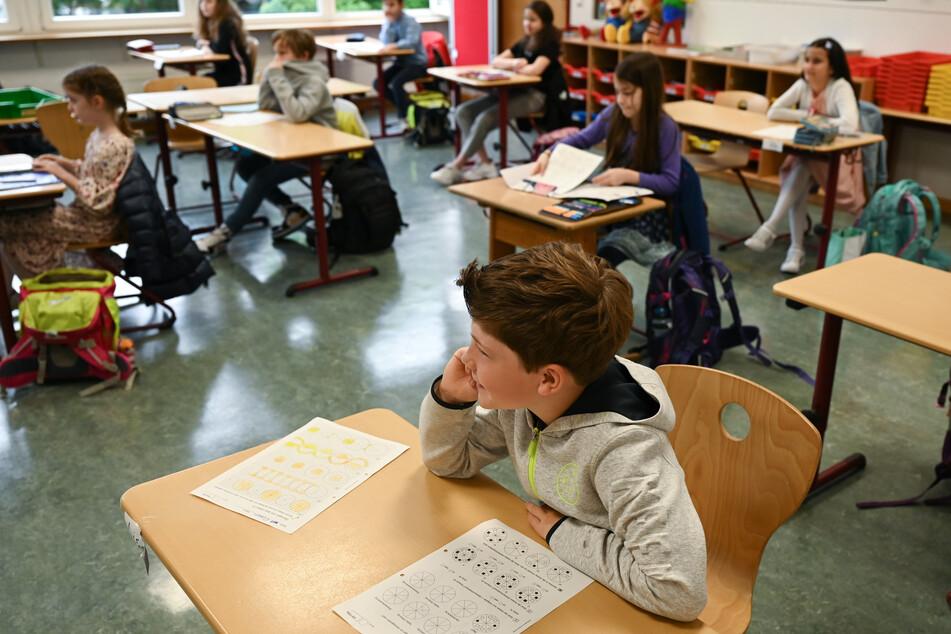 Schülerinnen und Schüler einer vierten Klasse sitzen beim Unterricht an Einzeltischen mit Abstand zueinander.