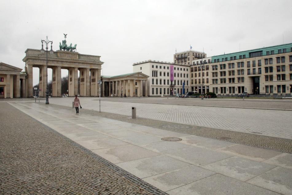 Einsam geht eine Frau zur Mittagszeit über den sonst sehr belebten Pariser Platz vor dem Brandenburger Tor.