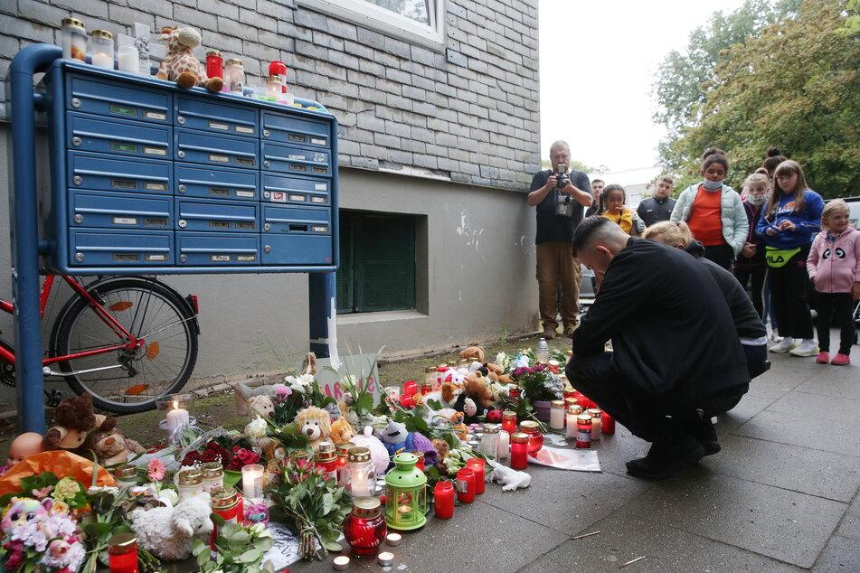 Trauende knien vor Blumen, Kerzen und Stofftieren vor dem Haus in Solingen, in dem am Vortag fünf tote Kinder aufgefunden worden waren.