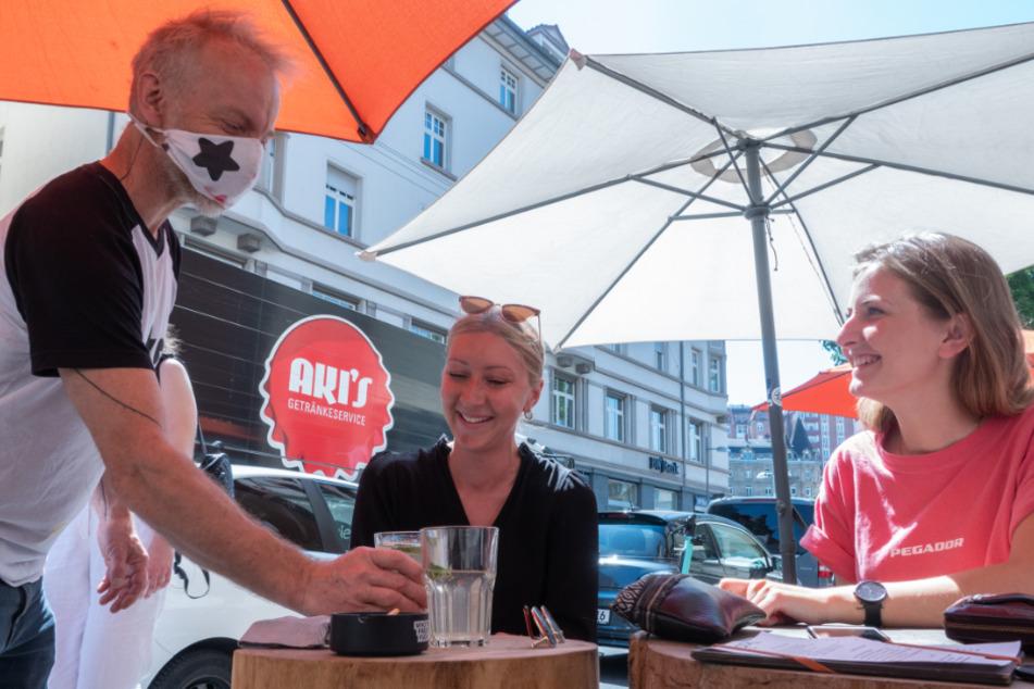 Zwei Frauen genießen im Freien Getränke in einem Café. (Symbolbild)