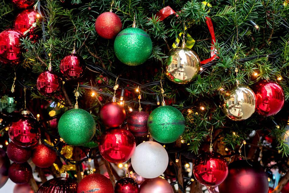 Christbaumkugeln hängen an einem Weihnachtsbaum.