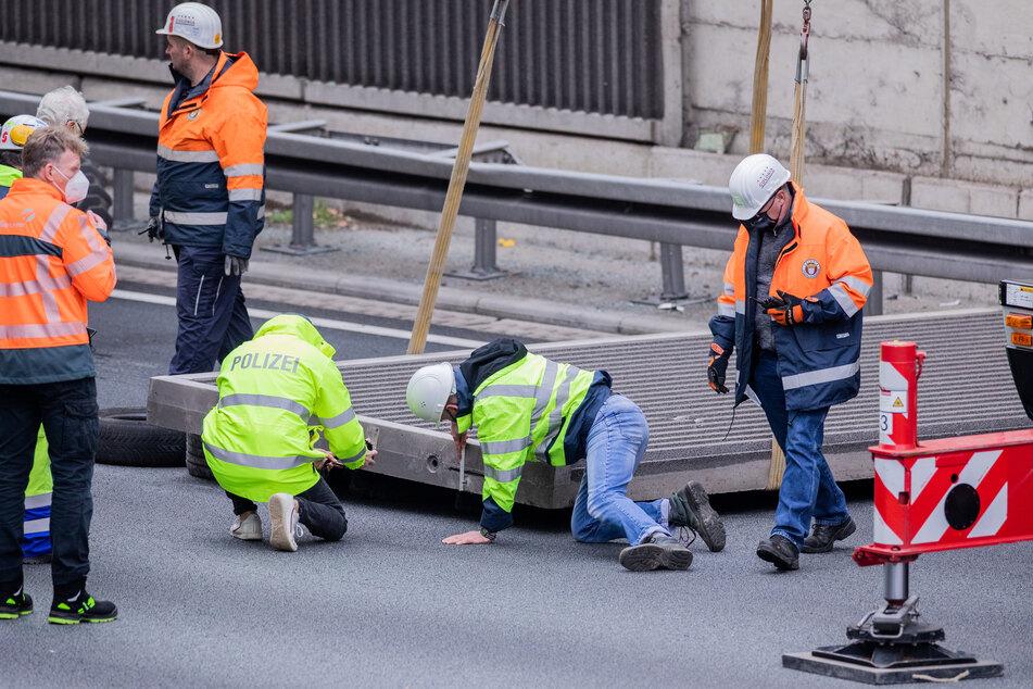 Polizeibeamte der Kriminalpolizei untersuchen eine Betonplatte auf der A3.