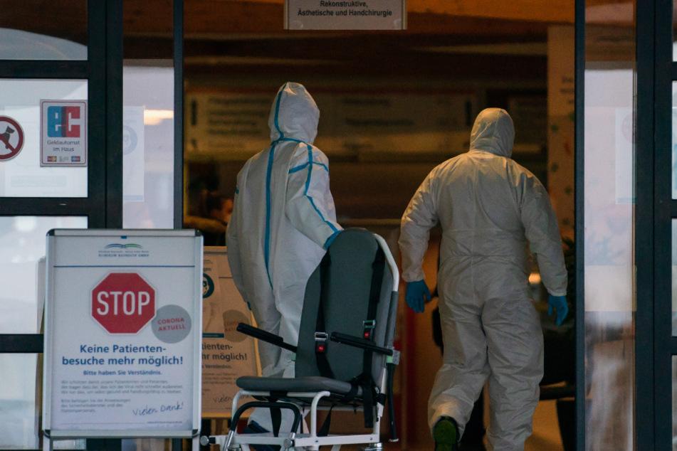 Bayreuth: Medizinisches Personal in Ganzkörperschutzanzügen geht in Richtung Haupteingang des Klinikums Bayreuth. Wegen des Verdachts des Ausbruchs einer hochansteckenden Corona-Mutation hat das Klinikum Bayreuth betroffene Häuser vorerst geschlossen.