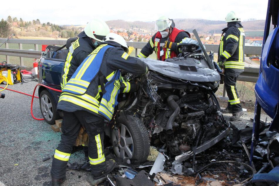 Einsatzkräfte der Feuerwehr stehen um den komplett zerstörten Audi.