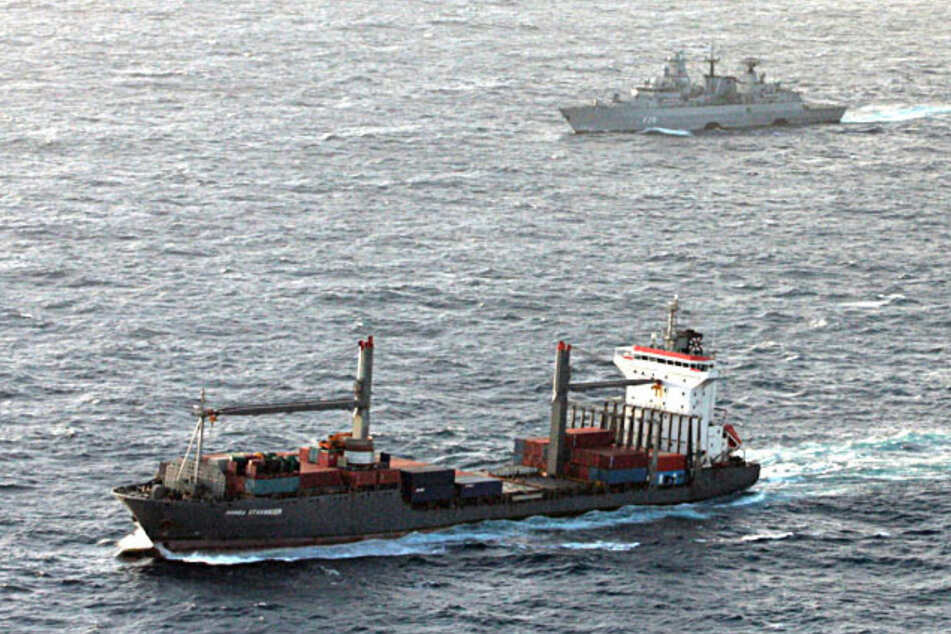"""Begleitet von der Fregatte """"Brandenburg"""" der Deutschen Marine (im Hintergrund) ist das Handelsschiff """"Hansa Stavanger"""" unterwegs zum kenianischen Hafen Mombasa. Das Containerschiff wurde am 4. April 2009 von somalischen Piraten gekapert. Nach vier Monaten kam das Schiff wieder frei."""
