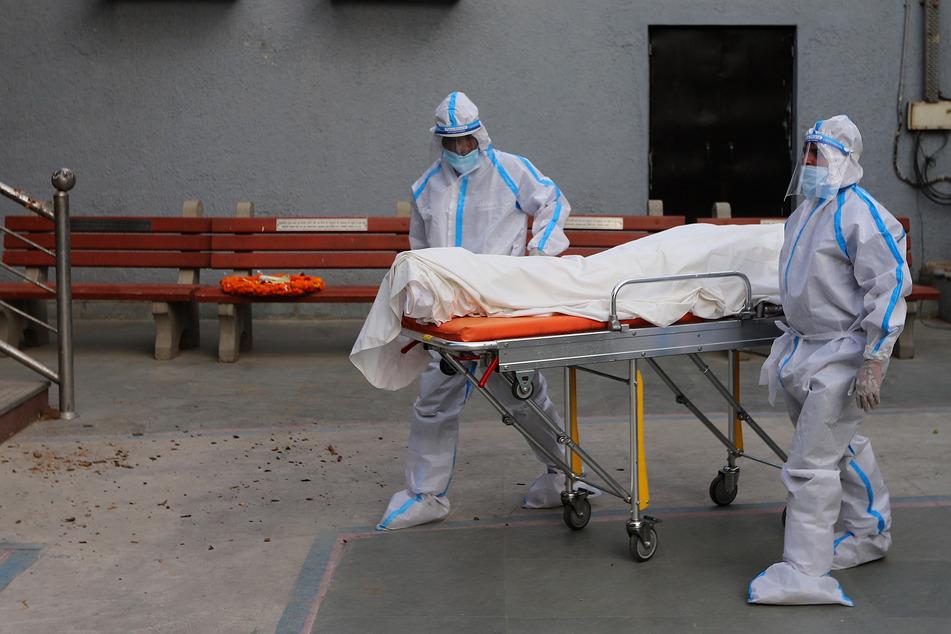 Zwei medizinische Mitarbeiter bringen die Leiche einer Person, die an den Folgen einer Corona-Infektion gestorben ist, auf einer Trage in ein Krematorium. Der Universität Johns Hopkins zufolge gibt es in Indien über 548.000 bestätigte Corona-Infektionen.