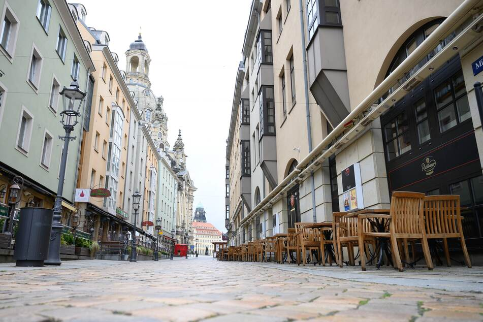 Leere Tische und Stühle stehen vor geschlossenen Lokalen auf der Münzgasse in Dresden.
