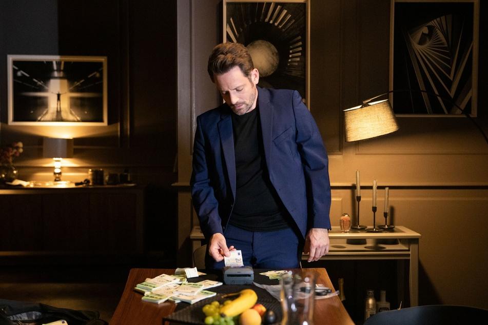 Justus prüft die Scheine aus Gieses Tasche und muss feststellen, dass es sich um Falschgeld handelt.