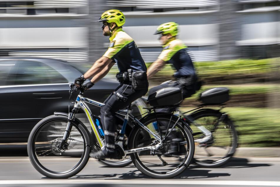 """Zwei Beamte der Fahrradstaffel des Frankfurter Polizeipräsidiums fahren mit ihren """"Streifenrädern"""" am Polizeipräsidium entlang."""