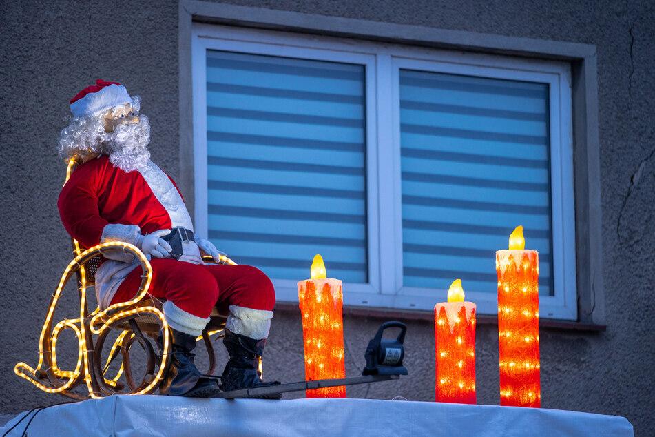 Eine beleuchtete Weihnachtsmannfigur sitzt auf Vordach eines Wohnhauses.