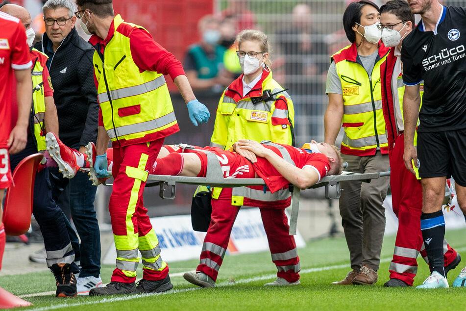 Berlins Timo Baumgartl (25, M.) wird nach einem Zusammenstoß mit Fabian Klos (33, r.) von Arminia Bielefeld vom Spielfeld getragen