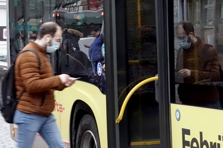 Mit Maske bekleidet betritt ein Mann einen Bus in Neumünster.