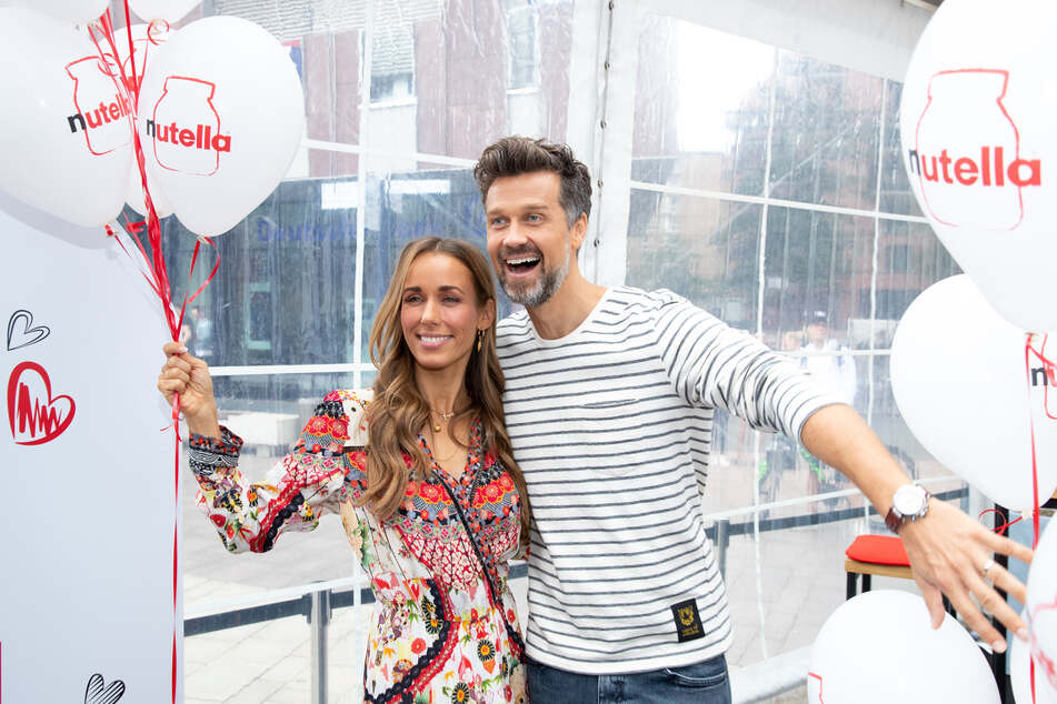 Wayne und Annemarie Carpendale bei der Eröffnung eines Pop-up-Café's posierend Arm in Arm.