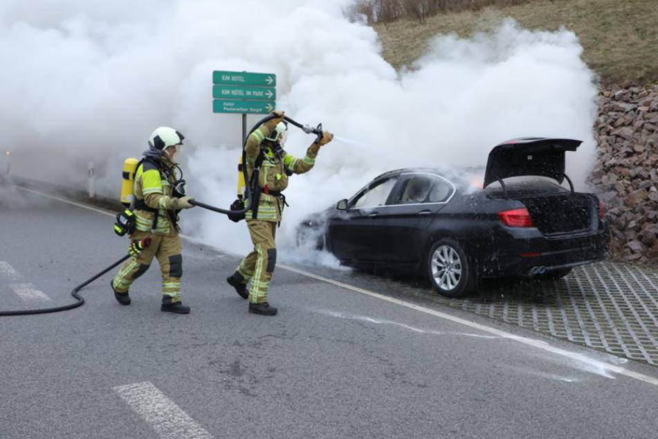 Einsatzkräfte der Feuerwehrlöschen den brennenden Wagen.