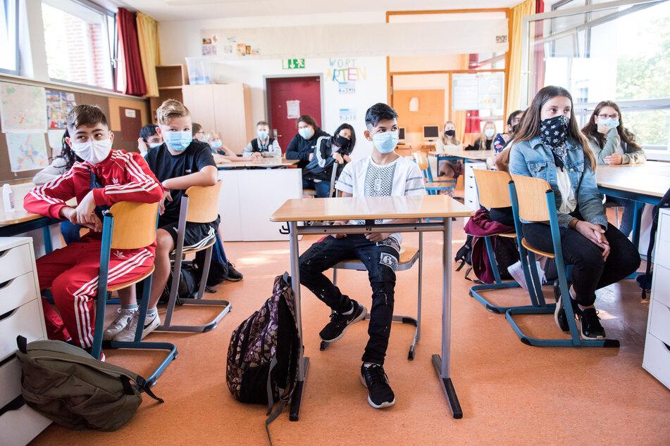 Schüler einer 7. Klasse der Max-Schmeling-Stadtteilschule sitzen zu Beginn des Unterrichts mit Mund-Nasen-Bedeckungen im Klassenraum.