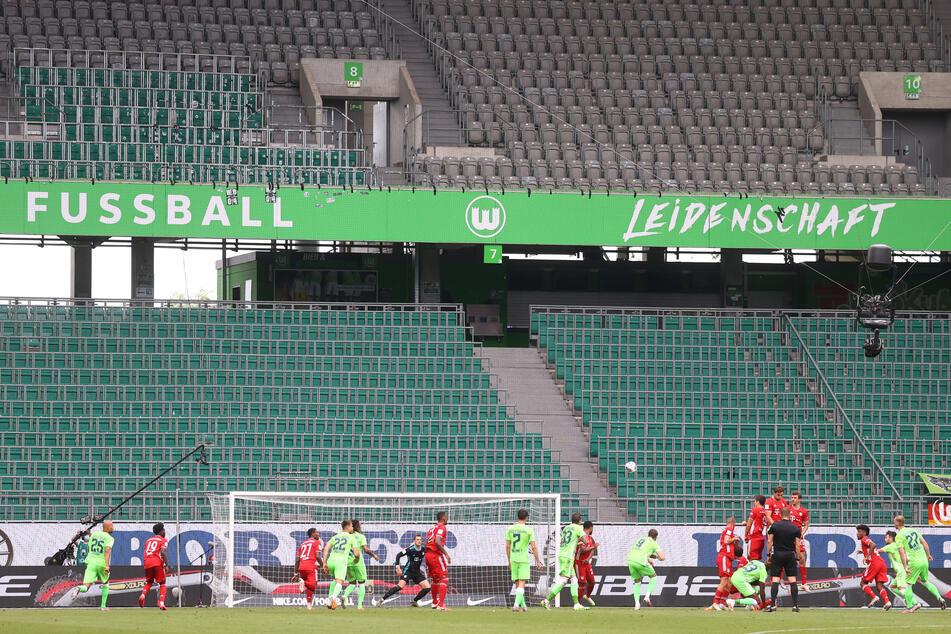 Spieler von VfL Wolfsburg und Bayern München in Aktion in der leeren Volkswagen Arena.