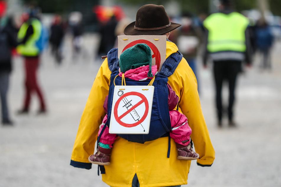 """Eine Teilnehmerin einer Protestkundgebung der Initiative """"Querdenken"""" trägt in Stuttgart ein Schild gegen Impfungen auf ihrem Rücken."""