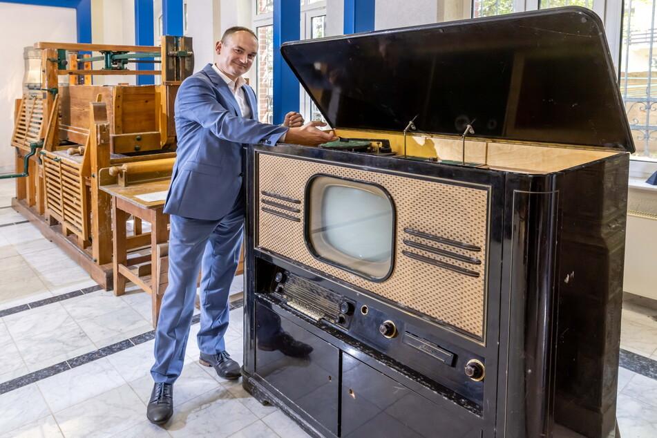 """GGG-Sprecher Erik Escher (39) präsentiert den Fernseh- und Radio-Schrank aus dem """"VEB Sachsenwerk"""" Radeberg."""