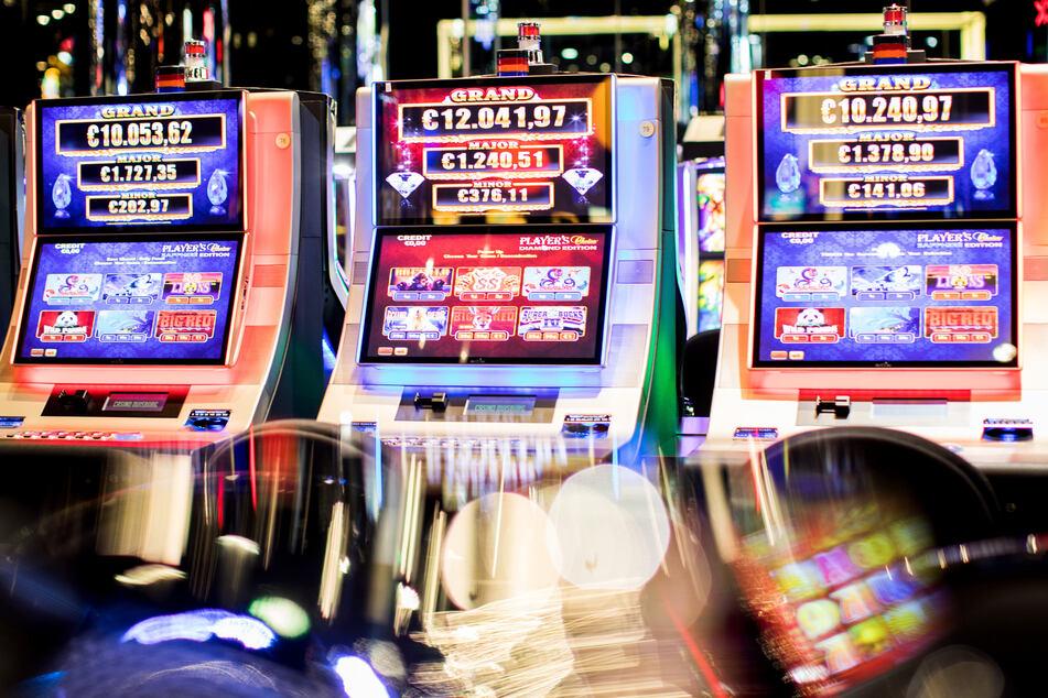 Spielautomaten in einer Casino-Halle. Die bunten Lichter bringen viele Menschen dazu, horrend viel Geld zu investieren.