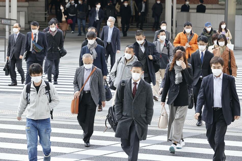 Pendler mit Mundschutz gehen im Geschäftsviertel Marunouchi in Tokio über eine Straße.