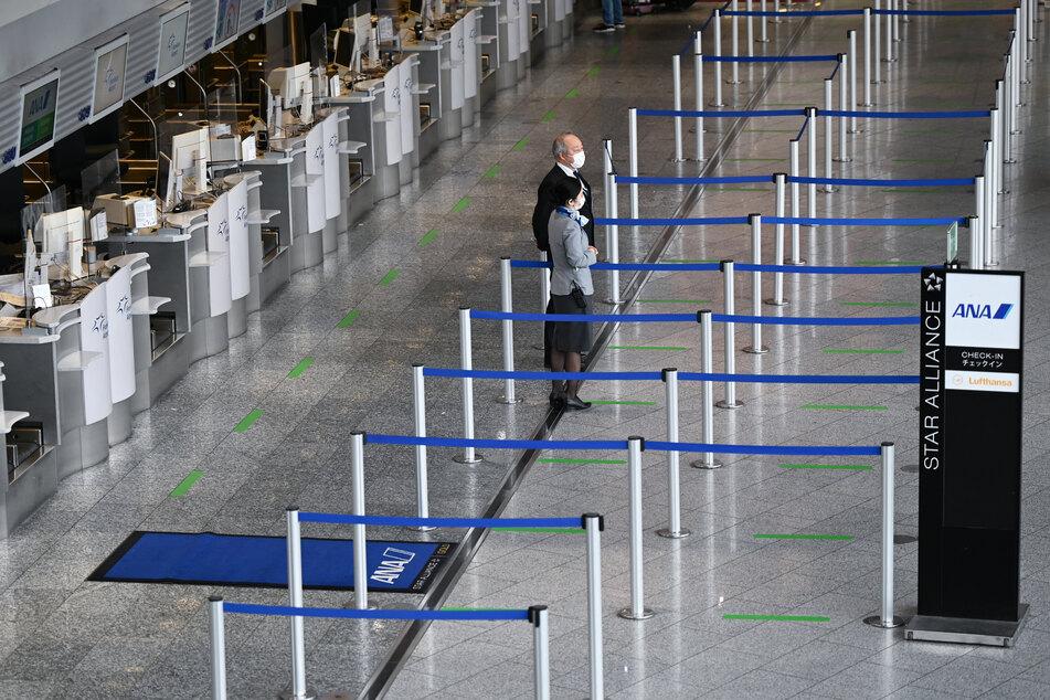 Mitarbeiter der Fluggesellschaft ANA stehen im Terminal 1 des Frankfurter Flughafens vor den leeren Abflugschaltern.