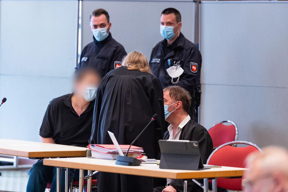 Der Angeklagte (l) spricht mit seinen Verteidigern im Gerichtssaal.