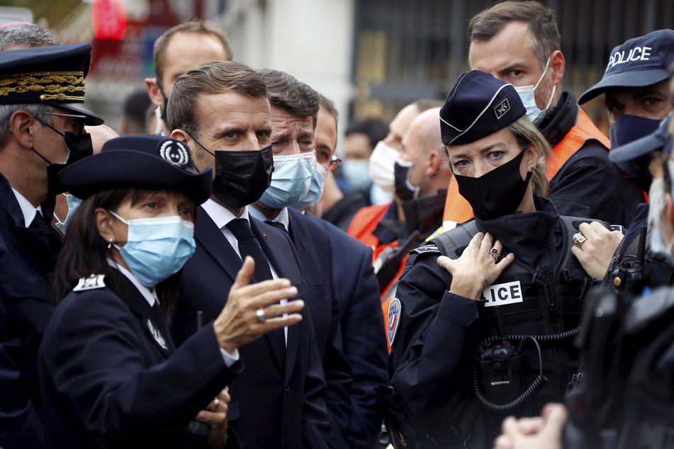 Emmanuel Macron (3.v.l), Präsident von Frankreich, und Christian Estrosi (4.v.l)), Bürgermeister von Nizza, sprechen nach der Messerattacke mit Polizeibeamten.