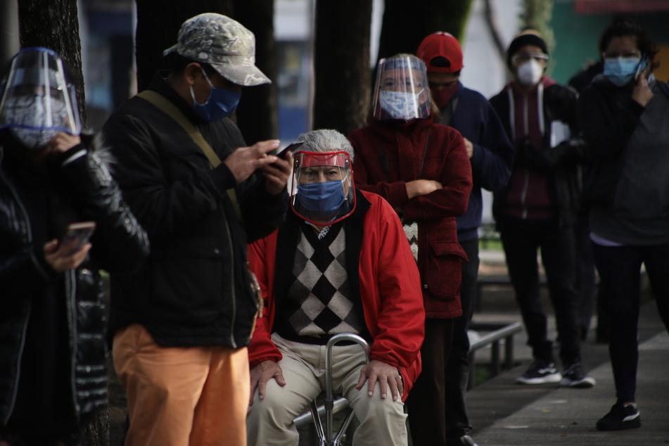 Menschen warten mit Mundschutz und Gesichtsvisieren vor einer Corona-Teststation in Mexiko-Stadt.