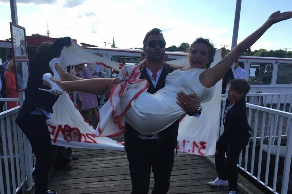 Musiker Sasha (49) trägt seine Frau Julia Röntgen auf ihrer Hochzeit über einen Bootssteg.