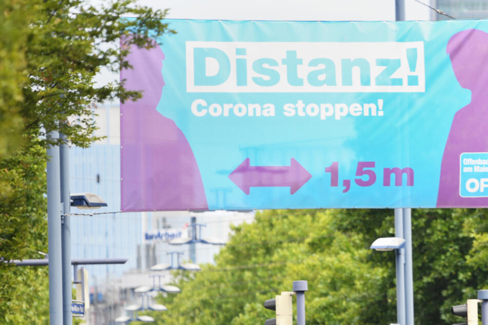"""Ein großes Plakat mit der Aufschrift """"Distanz! Corona stoppen!"""" prangt am Ortseingang von Offenbach."""