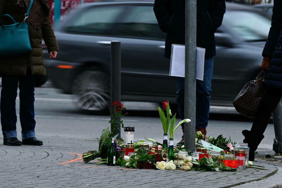 Blumen liegen an der Stelle, wo in Frankfurt-Sachsenhausen am 13. Februar 2021 zwei Fußgänger bei einem Autounfall ums Leben kamen.