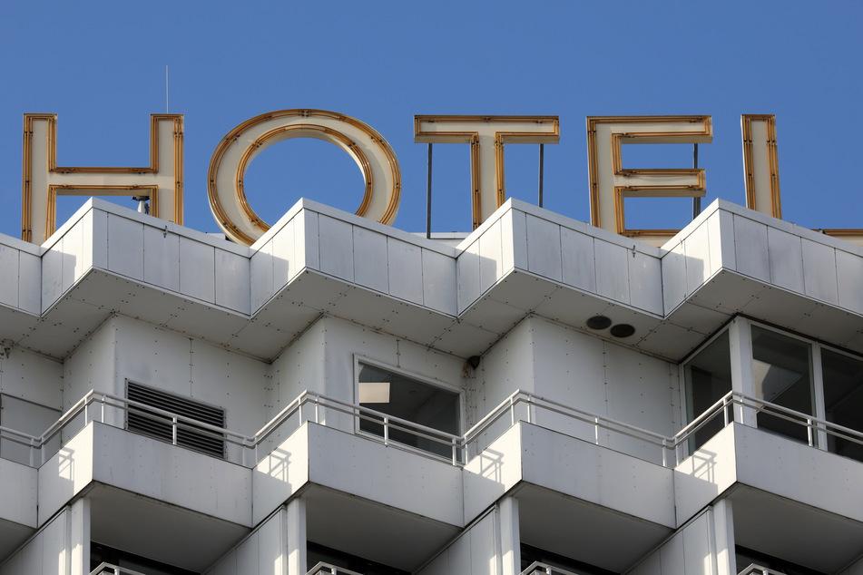 """Das Wort """"Hotel"""" in großen Leuchtbuchstaben auf dem Dach eines Hotels."""