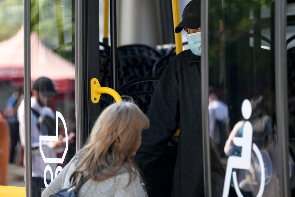 Ein junger Mann trägt einen Nasen-Mund-Schutz bei der Fahrt in einem Bus der BVG. Bald können Fahrgäste auch wieder vorne einsteigen.