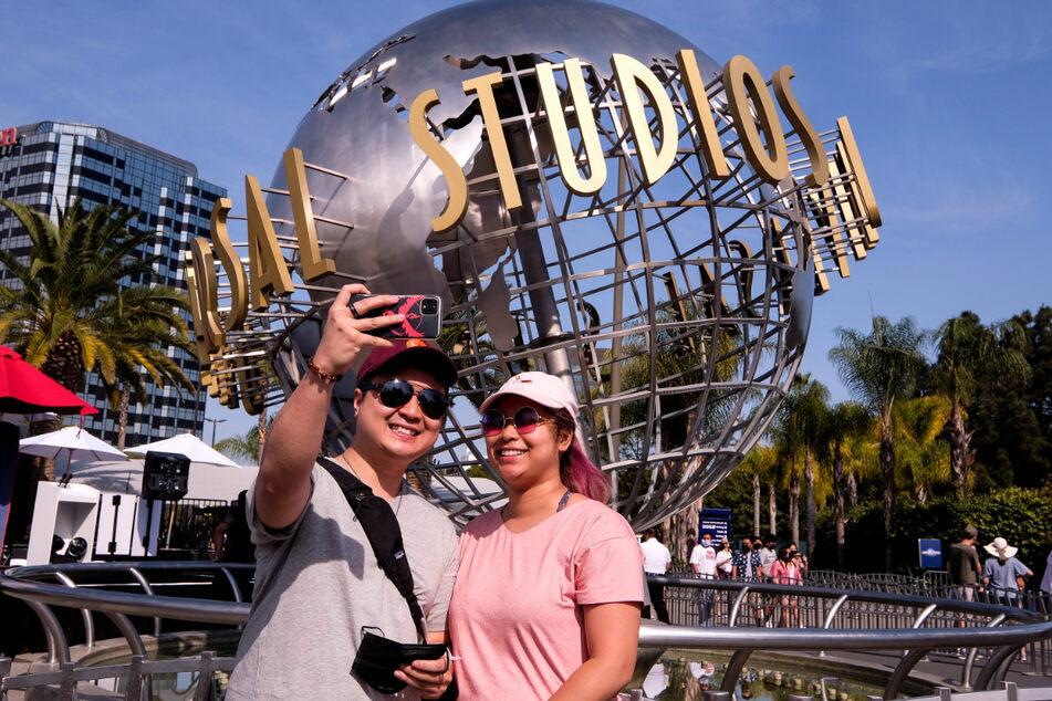 Ein Paar fotografiert sich vor dem Schriftzug Universal Studios Hollywood auf einer Weltkugel-Skulptur. Am Dienstag hob Kalifornien die meisten seiner Covid-19-Beschränkungen auf.