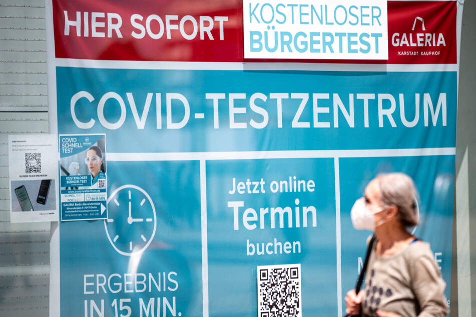 Eine Frau mit Maske läuft an einem Corona-Testzentrum am Alexanderplatz vorbei.