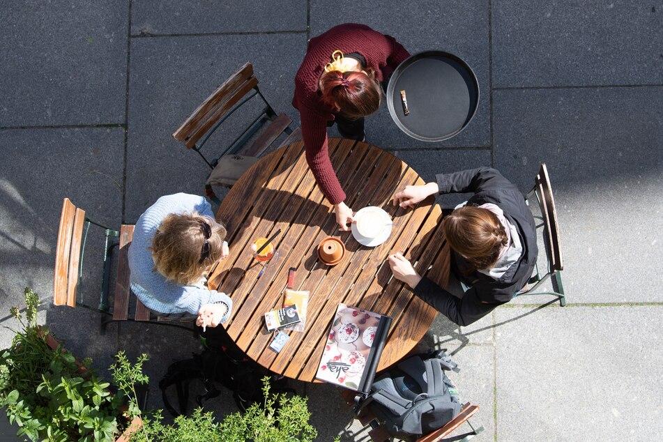 Eine Kellnerin bedient in einem Dresdner Cafe zwei Frauen.