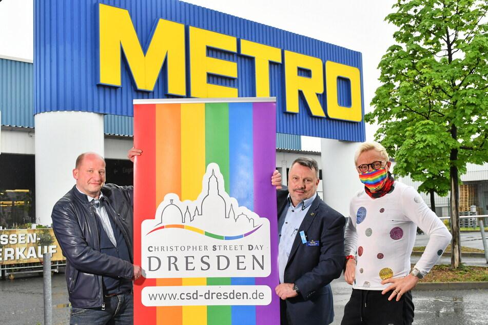 CSD-Chef Ronald Zenker (48, v.l.), Metro-Betriebsleiter Jens-Uwe Hauffe (51) und Unternehmer Wolle Förster (66) stellen ein Regenbogen-Plakat auf.