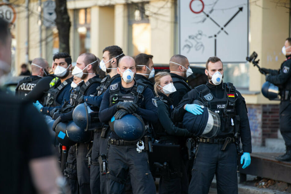 Polizisten mit Atemschutzmasken stehen auf dem Rosa-Luxemburg-Platz.