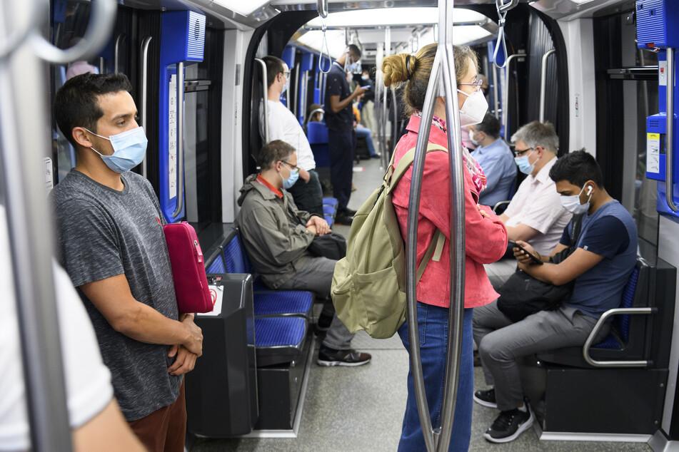 Passagiere tragen Mundschutze während einer Fahrt in einer Bahn.
