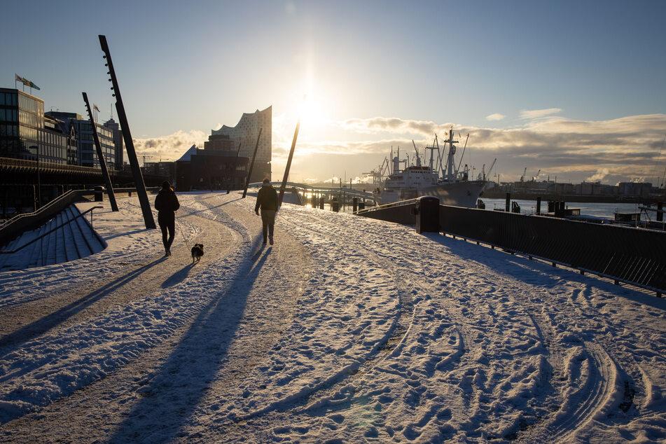 Passanten mit Hund sind auf der verschneiten Elbpromenade bei strahlendem Sonnenschein an den Landungsbrücken im Hafen unterwegs.