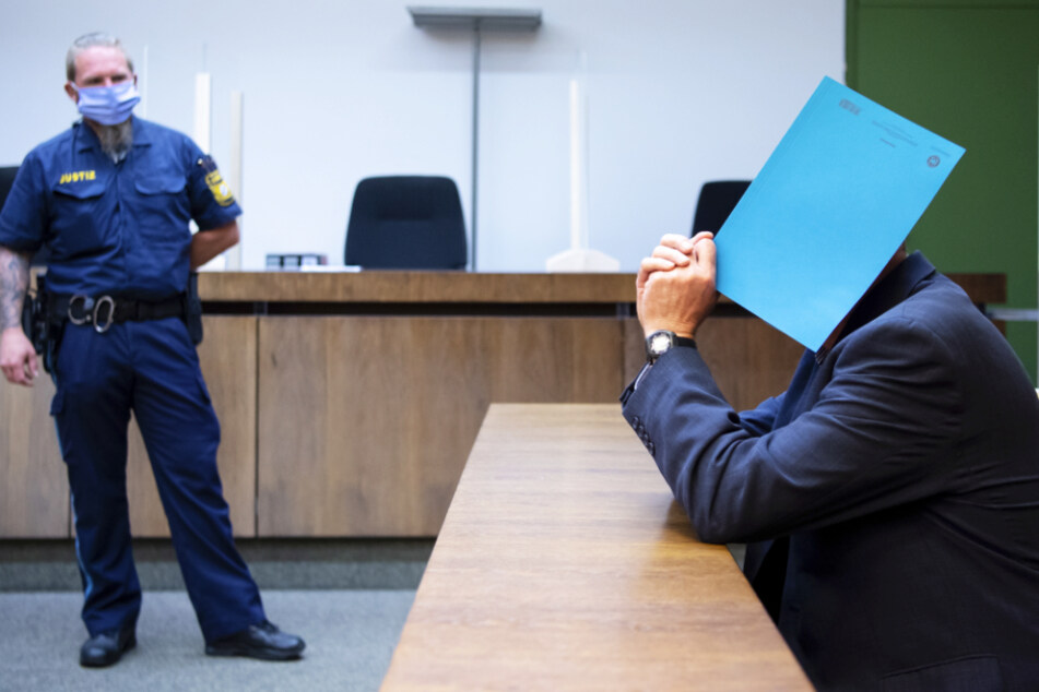 Der wegen sexuellen Missbrauchs von Kindern und Schutzbefohlenen sowie sexueller Nötigung angeklagte Mann (r.) sitzt auf seinem Platz.