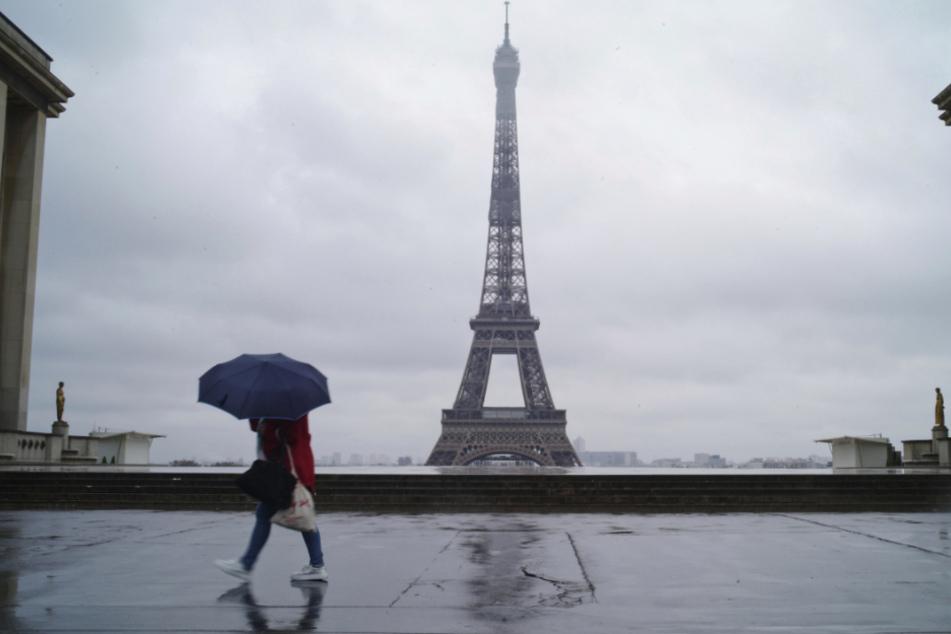 Eine Frau geht über den verlassenen Trocadero-Platz in Paris.