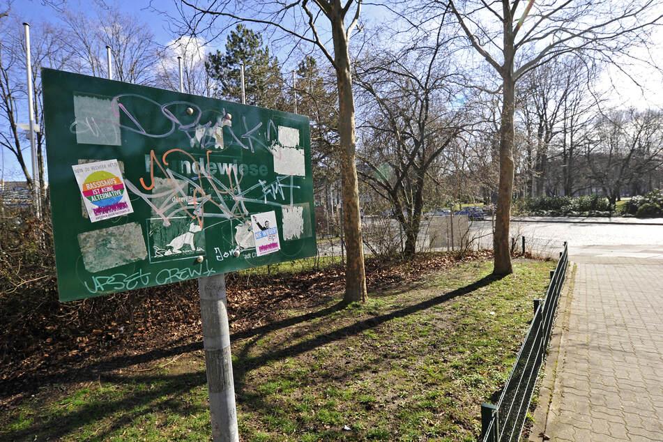 Das Schild der Hundewiese am Schillerplatz ist beschmiert, überklebt und kaum lesbar. Auf der Wiese liegen krustige Tretminen.