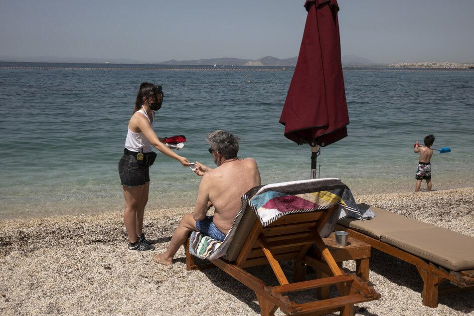 Eine Angestellte mit Mund-Nasen-Schutz weist einem Urlauber einen Platz am Strand zu.