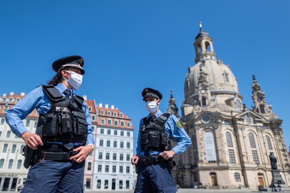 Polizeibeamte stehen mit Maske vor der Frauenkirche.